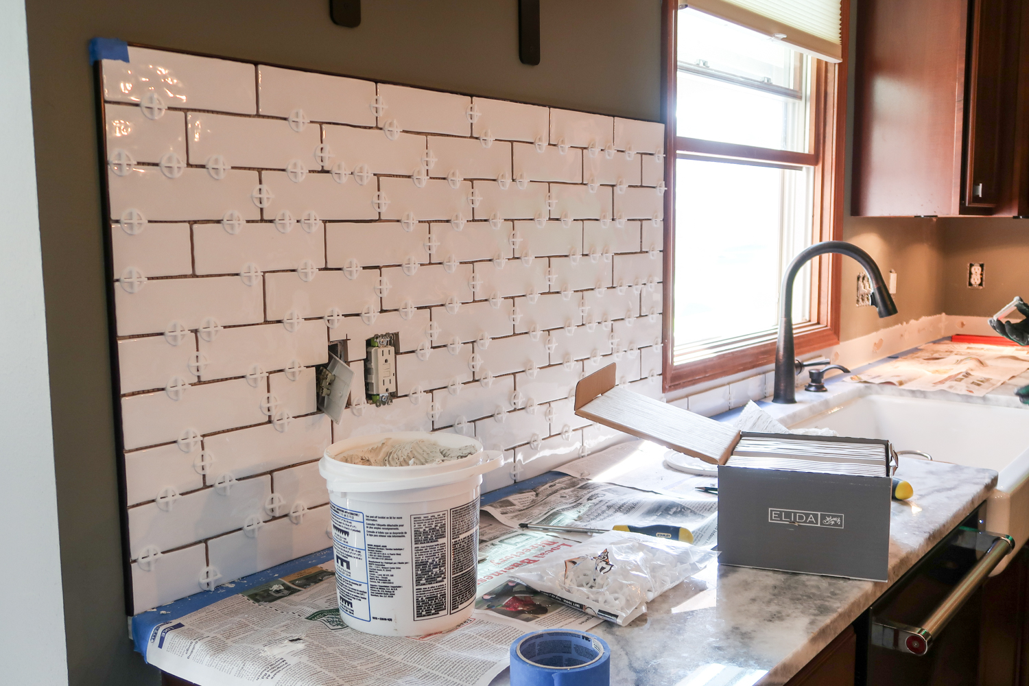 installing a white subway tile backsplash