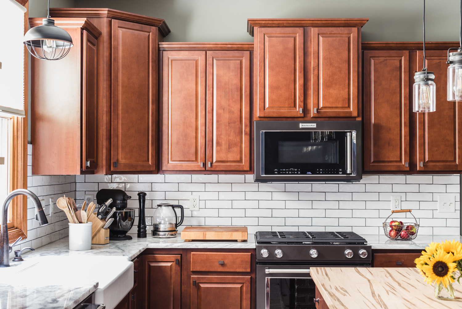 black stainless appliances in kitchen with white subway tile