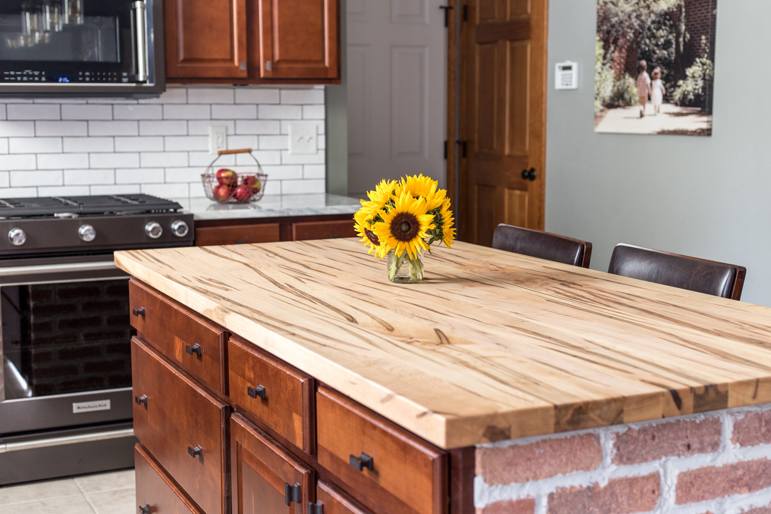 wooden countertop on brick island kitchen