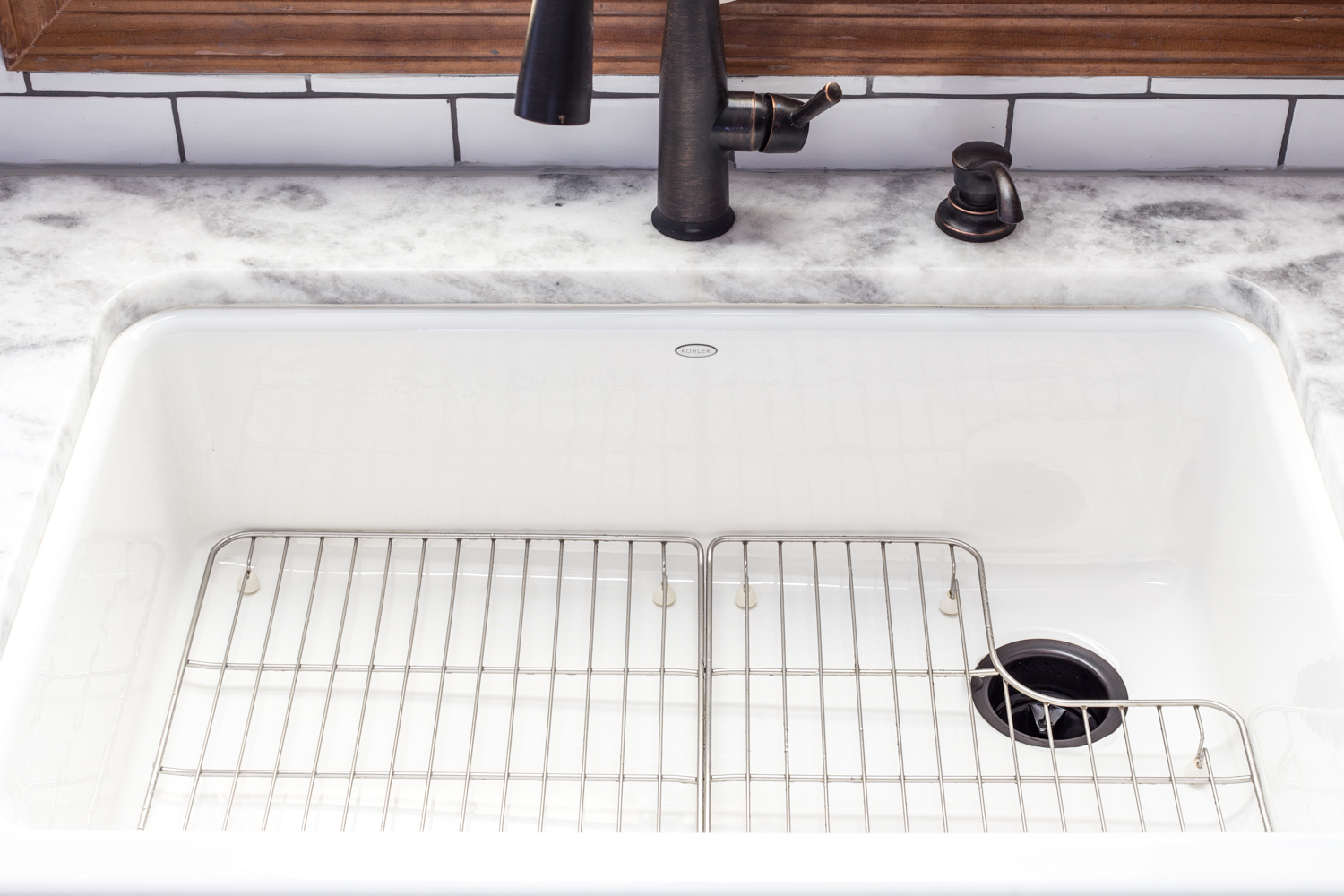 white farm sink with quartzite counter and white subway tile backsplash
