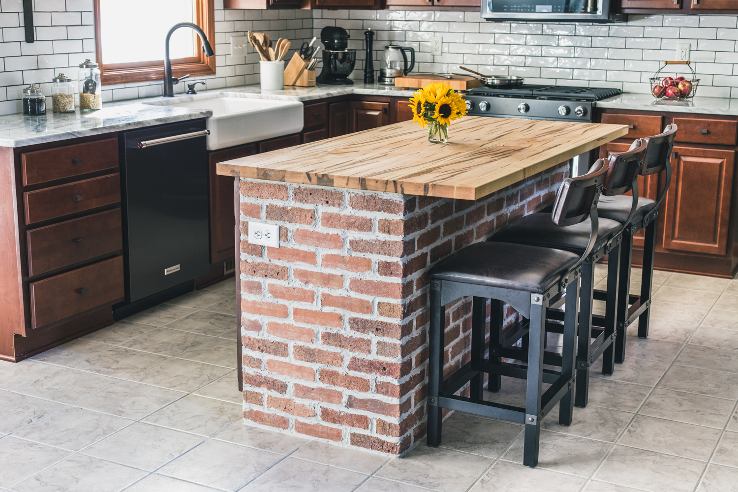 Kitchen Island With Exposed Brick And Wooden Countertop