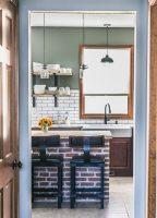kitchen with exposed brick island, open shelving, and white subway tile