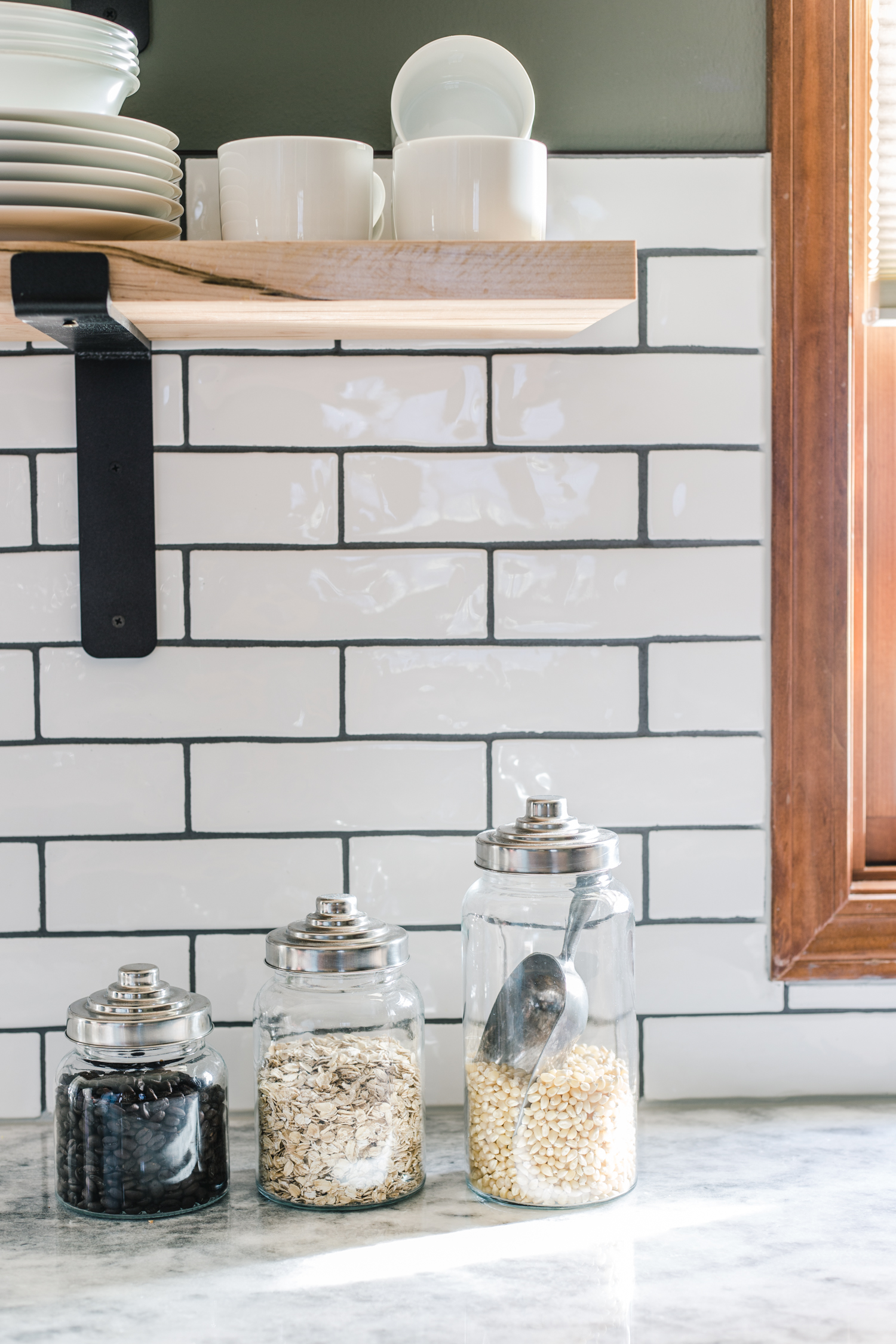 white subway tile with dark grout and floating shelves in kitchen