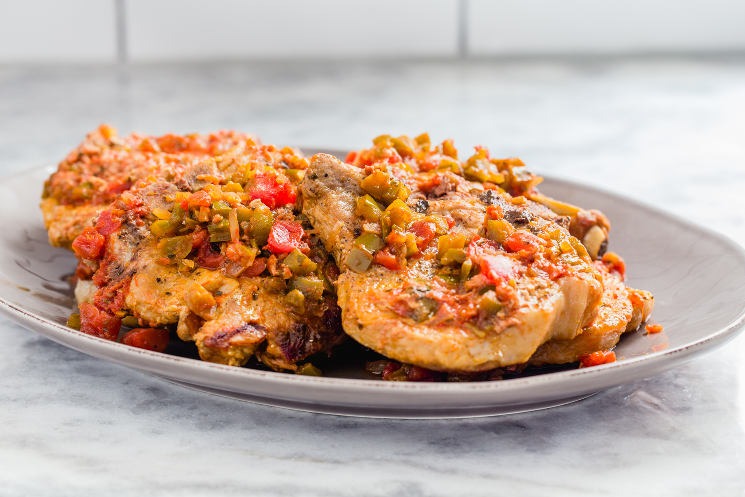 platter of pork chops with salsa on marble counter