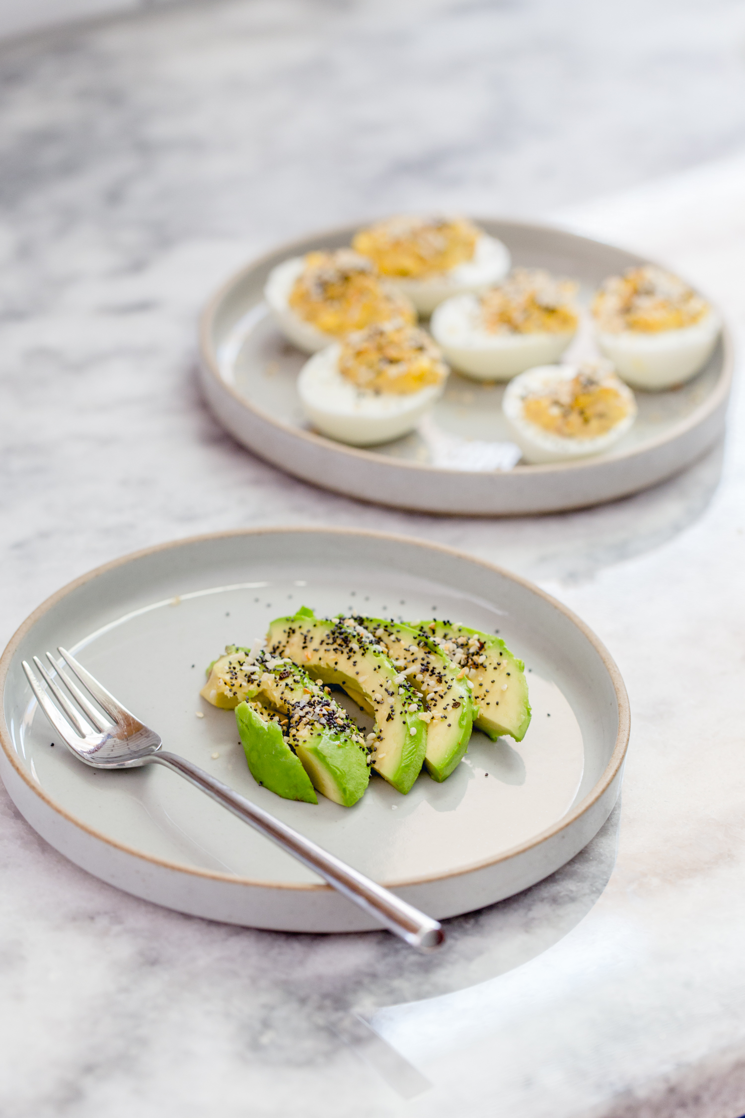 plate with sliced avocado and a plate with deviled eggs